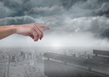 Hand pointing in cloudy sky over city Stock Photography