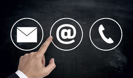 Hand pointing at contact options icons e-mail letter telephone.  Royalty Free Stock Photo