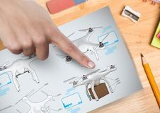 Hand pointing at a Drone DIY drawings plans. Digital composite of Hand pointing at a Drone DIY drawings plans Stock Images