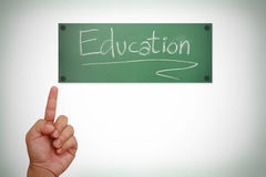 Hand pointing on education word on blackboard Royalty Free Stock Photography