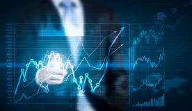 Hand pointing at financial chart. Businessman hand pointing at financial chart on blue background stock images