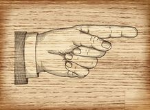 Hand with pointing finger. Vector EPS 10. Hand with pointing finger on wood texture. Illustration in retro style Stock Image