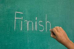 Hand pointing at finish word of success concept. On chalkboard stock photos