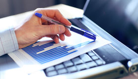 Hand pointing on a graph data. Selective focus Royalty Free Stock Photo