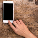 Hand pointing home button of smartphone Stock Image
