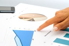 Hand pointing on investment documents. Close up of female hand pointing on investment documents Stock Images