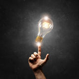 Hand pointing light bulb Royalty Free Stock Photos