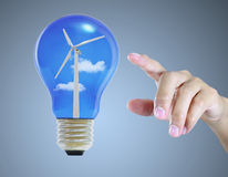 Hand pointing light bulb with wind turbine Royalty Free Stock Images