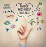 Hand pointing at Make Money Online concept. On light brown wall background Stock Photos