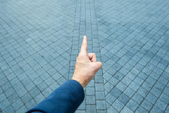 Hand pointing. Male hand pointing the finger forward to on grey brick Royalty Free Stock Photo