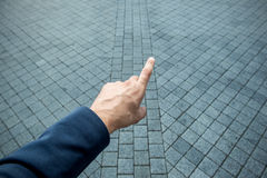 Hand pointing. Male hand pointing the finger forward to on grey brick Royalty Free Stock Images