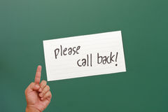 Hand pointing on please call back paper Royalty Free Stock Photography