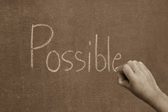 Hand pointing at possible word of success concept. On chalkboard Stock Photo