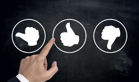 Hand pointing at rating icons with thumb.  stock photography