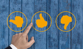 Hand pointing at rating icons with thumb.  stock image