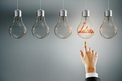 Leadership, idea and choice concept. Hand pointing at row of illuminated light bulbs on subtle background. Leadership, idea and choice concept royalty free stock photos