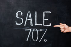 Hand pointing at seventy percent sale drawn on blackboard. Hand pointing on seventy percent sale drawn on blackboard with chalk Stock Image