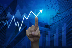 Hand pointing to arrow business chart and graph over map and cit Stock Photo