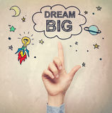 Hand pointing to Big Dream concept. On light brown wall background Royalty Free Stock Images