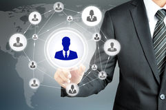 Hand pointing to businessman icon in the middle that linked with each other as network Stock Photo