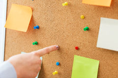 Hand pointing to cork board with stickers and pins Royalty Free Stock Photography