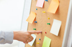 Hand pointing to cork board with stickers and pins Royalty Free Stock Image