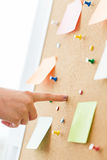 Hand pointing to cork board with stickers and pins Stock Photography