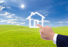 Hand pointing to house icon Royalty Free Stock Images