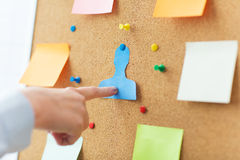 Hand pointing to human shape on cork board Stock Photo