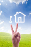 Hand pointing to key and house icon Stock Photo
