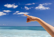 Hand pointing to the sky. Female hand against a beautiful blue sky pointing somewhere Royalty Free Stock Photo