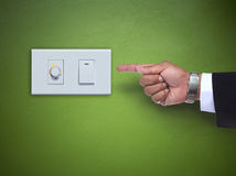 Hand pointing to switch ofelectric appliance on green wall Stock Photos