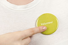 Hand pointing to volunteer button. Closeup on female hand pointing to green volunteer button Stock Photography