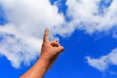 Hand pointing or touching to something on blue sky background.  royalty free stock image