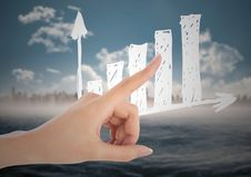 Hand pointing at white graph against blurry skyline and water Royalty Free Stock Images