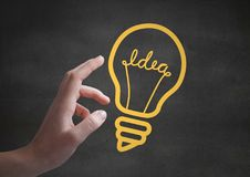 Hand pointing at yellow lightbulb graphics against grey wall