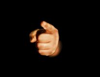 Hand pointing at you. A hand pointing at the viewer, black background Royalty Free Stock Image