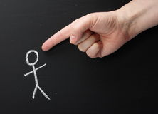 Hand Pointing at You. A giant hand pointing the index finger at a chalk stick figure on a blackboard Stock Photography