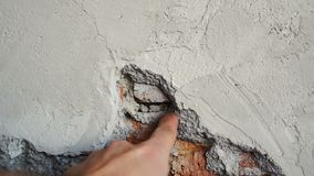 Hand points to cement in brick wall