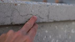 Hand points to crack in concrete wall