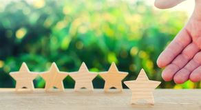 Hand points to the fifth wooden star. Get the fifth star. The concept of the rating of hotels and restaurants, the evaluation of c. Ritics and visitors. Quality royalty free stock photo