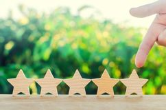 Hand points to the fifth wooden star. Get the fifth star. The concept of the rating of hotels and restaurants, the evaluation of c. Ritics and visitors. Quality stock photography