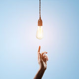 Hand points to light bulb Royalty Free Stock Images