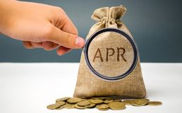 A hand points to a money bag with the word Apr. This is a financial fee, expressed as an annual rate. Applicable to loan, mortgage stock photos