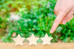 The hand points to the third star on a green background. Rating, level of quality. Universal recognition, success and high efficie. Ncy. Evaluation of the hotel royalty free stock photography