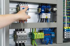 Hand points towards switchboard or control cabinet - electronics. Colorful fuses, technical picture Royalty Free Stock Photos