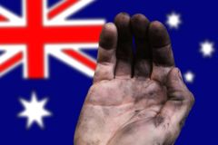 Hand of a poor man against the background of the flag of Australia. Poverty in Australia. The problem of poverty and poverty of people in the world stock photos
