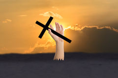 Hand pop up from ground. And holding the cross with  Silhouette of  sky and cloud Stock Photography