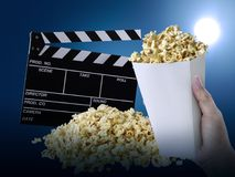 Hand with Popcorn, Movie clapperboard, on at blue background royalty free stock photography