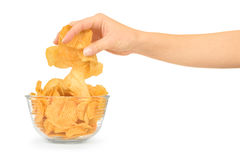 Hand with potato chips and bowl Stock Images